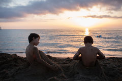 Young child boy and his friend or brother playing with sand at beach covering himself.Warm sunset light. Family summer Royalty Free Stock Photos