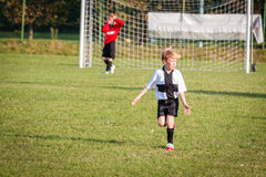 Young child boy playing soccer. Young child boy (8-9) playing soccer during organized team league game royalty free stock image