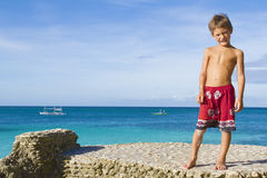 Young child boy on rocks on tropical sea backgroun Royalty Free Stock Photos