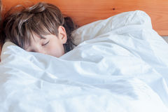 Young child boy sleeping in bed at home,. Indoor portrait Royalty Free Stock Photos