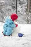 Young child building a snowman Royalty Free Stock Photo