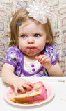 Young child celebrating her first birthday. Girl eating a slice of cake and making a mess Stock Photo