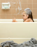 Young child cleaning in the tub. Image shows young girl covered in soap suds getting clean while taking a bath Stock Images