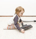 Young child cleaning vacuum cleaner Royalty Free Stock Photos