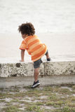 Young child climbing. Young African American child climbing on a ledge Stock Photography
