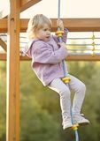 Child climbing rope on playground. Young child climbing rope on playground Royalty Free Stock Image
