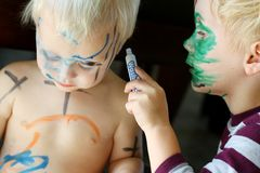 Young Child Coloring Baby Brother's Face. A young child his carefully coloring with a marker all over his baby brother's face and skin Stock Photography