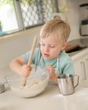 A young child is cooking in a domestic kitchen. Royalty Free Stock Photography