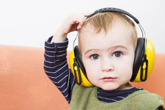 Young child on couch with earmuffs Royalty Free Stock Images