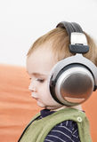 Young child on couch with headphone Stock Image