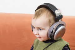 Young child on couch with headphone Royalty Free Stock Photography
