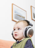 Young child on couch with headphone Royalty Free Stock Image