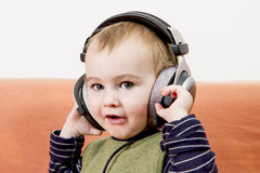 Young child on couch with headphone Royalty Free Stock Photos