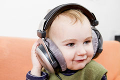 Young child on couch with headphone Royalty Free Stock Images