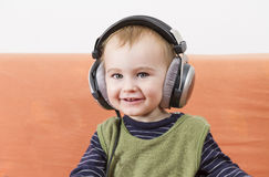 Young child on couch with headphone Stock Photography