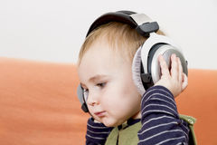 Young child on couch with headphone Royalty Free Stock Photo