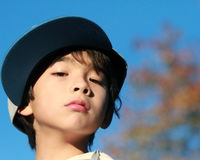 Young child defiance and confidence. Portait of a 10 years old boy with a baseball cap looking at you with confidence and defiance royalty free stock image