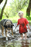 Young Child and Dog Playing in Muddy River Royalty Free Stock Photos