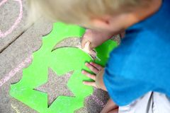 Young Child Drawing Outside with Sidewalk Chalk Royalty Free Stock Image