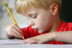 Young Child Drawing with Paper and Pencil Stock Image