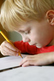 Young Child Drawing on Paper with Pencil Stock Photos
