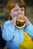 Young Child Eating Hamburger. Little girl eating hamburger. Vertically framed shot Royalty Free Stock Image