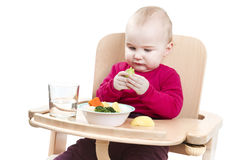 Young child eating in high chair Royalty Free Stock Photos