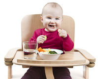 Young child eating in high chair Royalty Free Stock Images