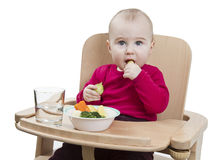 Young child eating in high chair Royalty Free Stock Image