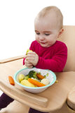 Young child eating in high chair Stock Photos
