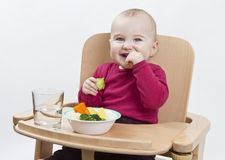 Young child eating in high chair Stock Photography