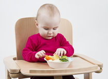 Young child eating in high chair Stock Photo