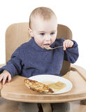 Young child eating in high chair. Isolated in white backgound Royalty Free Stock Photo