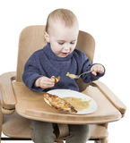 Young child eating in high chair. Isolated in white backgound Stock Images