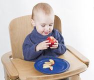 Young child eating peaches in high chair Royalty Free Stock Photography