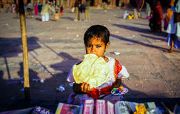 Young Child at Eid Festival in Fatehpur Sikri, India. A young girl eating a snack at Fatehpur Sikri during the festival of Eid al-Fitr. Uttar Pradesh, India Royalty Free Stock Photography