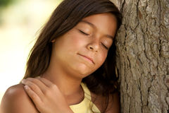 Young child enjoying nature. Young female child enjoying nature with her head next to a tree Royalty Free Stock Image