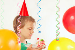 Young child in festive hat eating birthday cake Stock Image