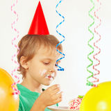Young child in festive hat eating piece of birthday cake Royalty Free Stock Image