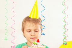 Young child in festive hat tasting piece of birthday cake Royalty Free Stock Photography