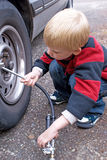 Five year old child filling a car tire with air. Royalty Free Stock Photos