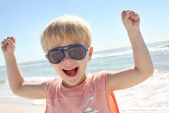 Young Child Flexing Muscles on Beach Royalty Free Stock Photography