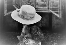 Silhouette. Young child gazing out rustic window dreamily. White, wide brim hat with floral dress and bow. Long hair flows beneath hat stock images