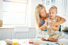 Young child getting help to knead bread dough. Young female child seated cross legged on kitchen table getting help to knead bread dough with enthusiastic woman Royalty Free Stock Images