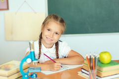 Young child girl drawing or writing with colorful pencils in not. Ebook in school over blackboard royalty free stock images