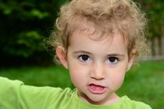 Young child, girl, in green top looking straight at camera. Royalty Free Stock Photos