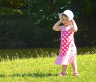 Young child, girl holding hat on. Royalty Free Stock Image