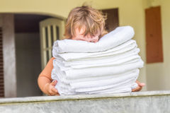 Young child girl holding rolled beach or spa towels on outd. Young cute child girl holding rolled beach or spa towels on outdoor house terrace Royalty Free Stock Photography