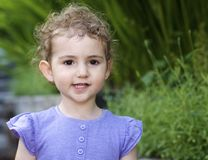 Young child, girl, in lilac top looking straight at camera. Royalty Free Stock Images