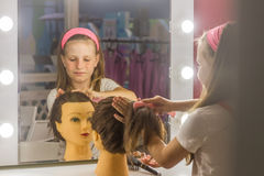 Young child girl making a hair style as a hairdresser stock image